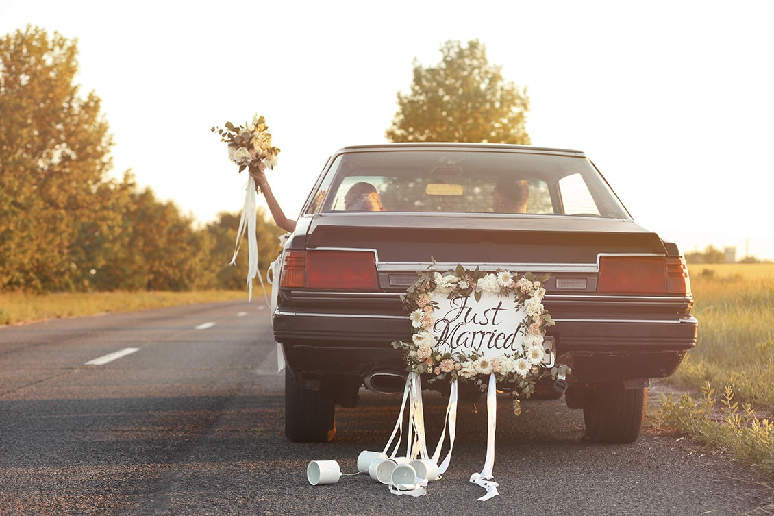 A couple driving down the road with cans tied to a 'Just Married' sign on the back of the car. The bride is throwing her bouquet out the window.